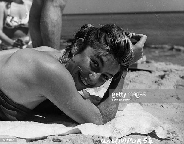 Anouk Aimee,, the film actress takes in the sun on the beach