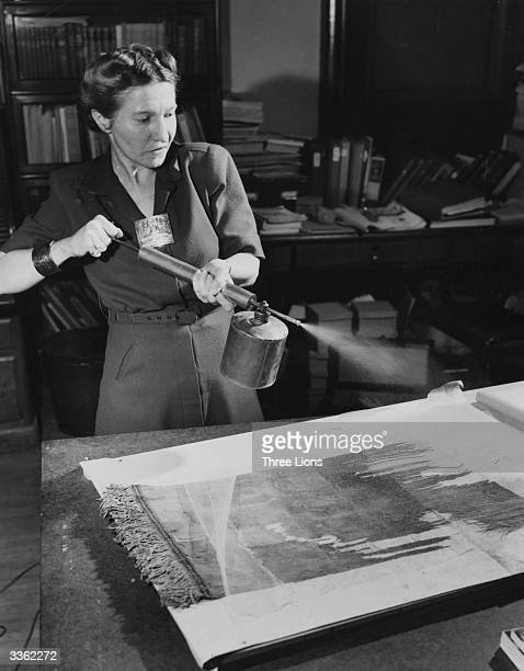 At work restoring Andean textiles Mrs Van Houten applies a spray of synthetic rosin dissolved in acetone to cement a thin silk netting to the back of...