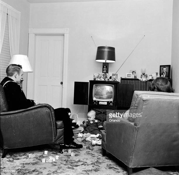 Bobby and Minnie West watch the television while their daughter Dian plays with her Christmas presents