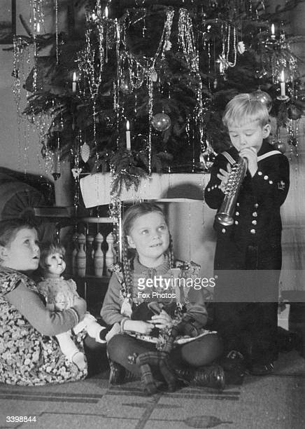 Children opening their Christmas presents under a Christmas tree