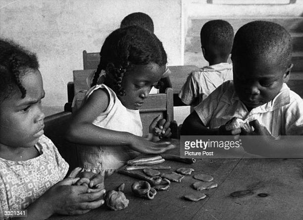 Children playing with plasticine in a scene from the Crown Film Unit film 'Caribbean' Original Publication Picture Post 5693 Who Hates The Crown Film...
