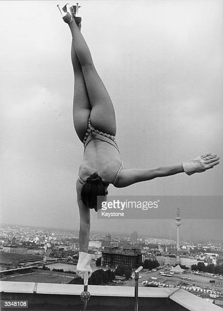 Circus performer Sylvia Teron performing her act on the roof of a skyscraper building in Hamburg