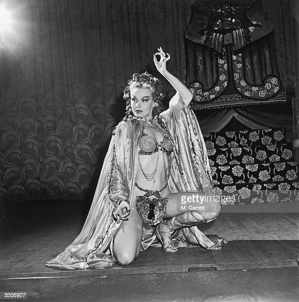 EXCLUSIVE Fulllength image of American exotic dancer Lili Saint Cyr kneeling in a pose with one arm up at the Follies Theatre in Los Angeles...