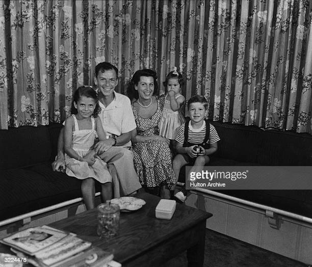 Family portrait of American singer and actor Frank Sinatra sitting on a couch with his first wife Nancy Barbato and their children Nancy Tina and...