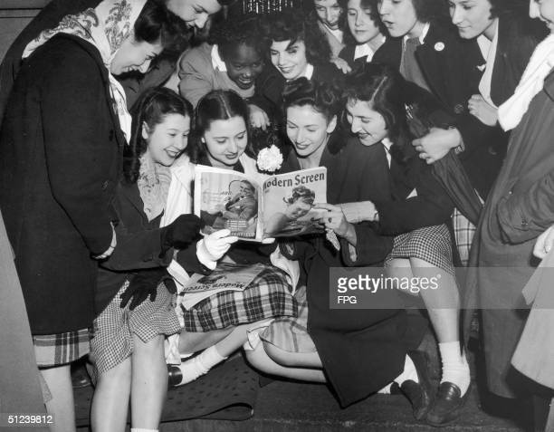 Circa 1950 Female fans of Frank Sinatra gaze adoringly at a picture of him in a copy of Modern Screen magazine whilst awaiting his appearance at the...