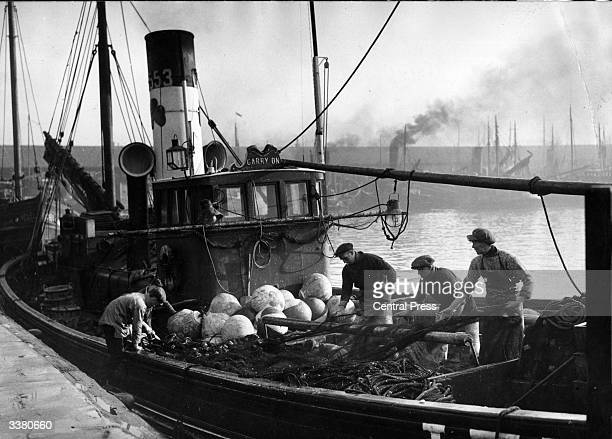 Fishermen preparing their nets on board a trawler at Lowestoft