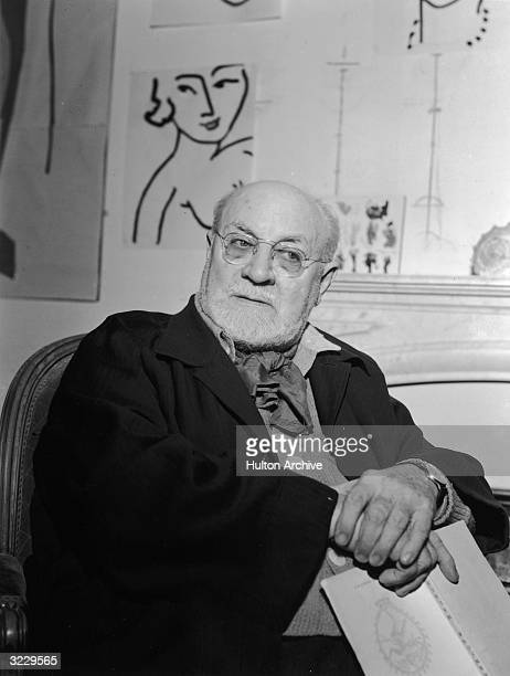 French artist Henri Matisse holds a book while sitting at his villa, 'Le Reve,' in Vence, near Nice, South of France. A line drawing of a woman hangs...