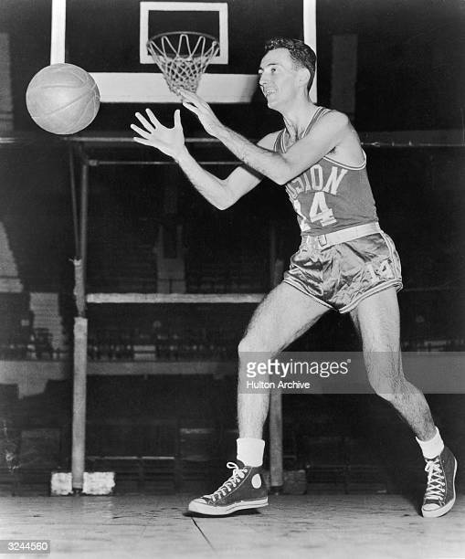 Fulllength image of American basketball player Bob Cousy guard for the Boston Celtics catching a ball on court