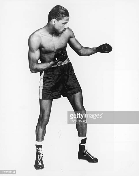 Fulllength profile view of American boxer and world welterweight champion Sugar Ray Robinson posing in a fighting stance on a white background