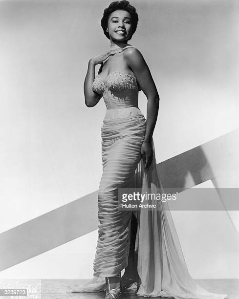 Fulllength studio portrait of American actor Diahann Carroll wearing an evening gown with a long sash She holds one hand by her shoulder