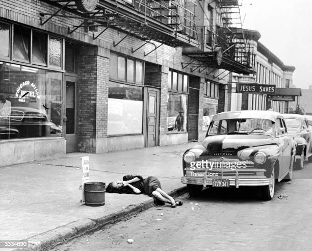 Having just somehow avoided a police clearance of destitutes on this American street a woman lies prone on the pavement A makeshift sign next to her...