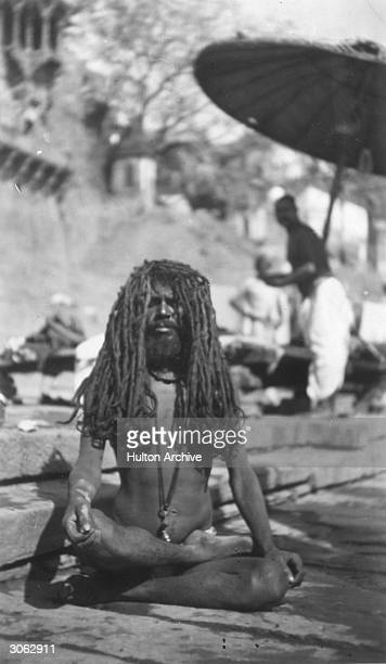 In Benares the sacred city of the Hindus by the Ganges a longhaired yogi sits cross legged naked except for a loincloth