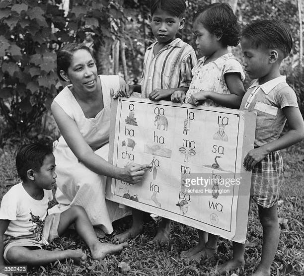 J L Harris principal of the Methodist Mission Agriculture and Training Centre at Nanga Mujong Sarawak teaching Iban children to read with a phonetic...