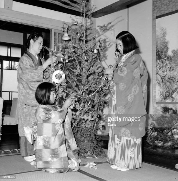 Japanese Christians wearing traditional kimonos decorate their christmas tree in a Yokahama home