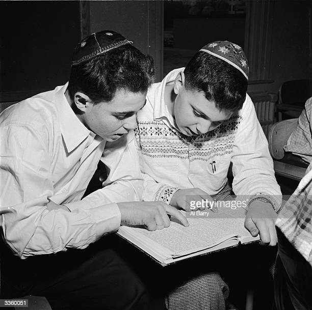 Jewish students celebrating the spring festival of Purim by reading the Megillah in the synagogue