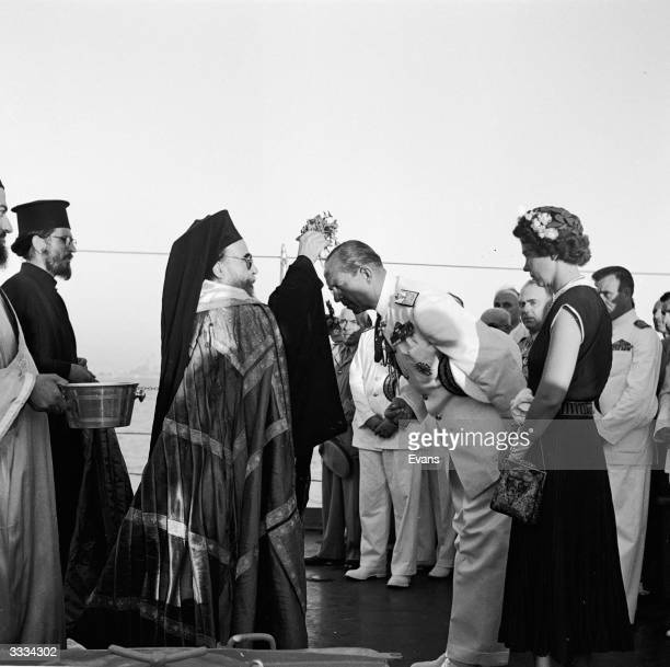 King Paul of Greece and his wife Queen Frederika being received by priests during a customary religious ceremony aboard a cruiser in the harbour of...