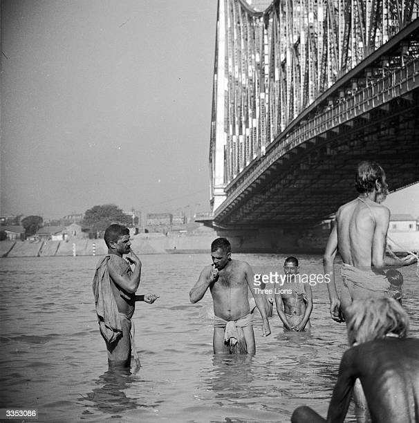 Men bathe in the Hooghly River Calcutta under the shadow of the Howrah bridge