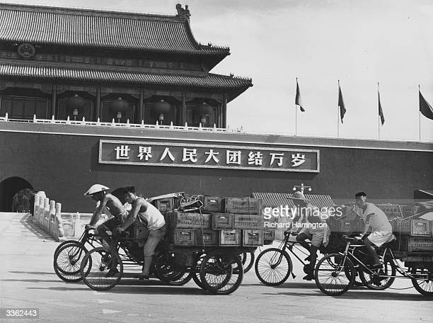 Men cycling pedicabs loaded with crates in Tiananmen Square Peking outside the Gate of Heavenly Peace