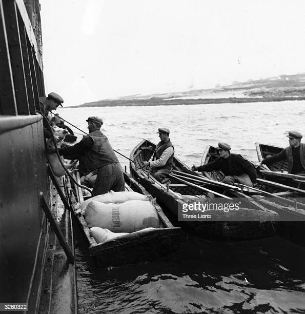 Men from the Aran Islands in County Galway row out to the larger boat to exchange their flour for pigs