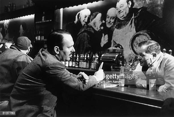 Novelist and essayist Robert Ruark talks with a barman in a New York bar