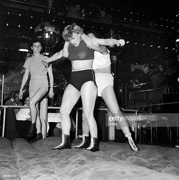 On Hamburg's Reeperbahn two women wrestlers perform in front of a night time audience