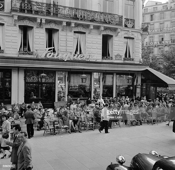 People sitting at tables outside Fouquet's a cafe in Paris' Champs Elysees