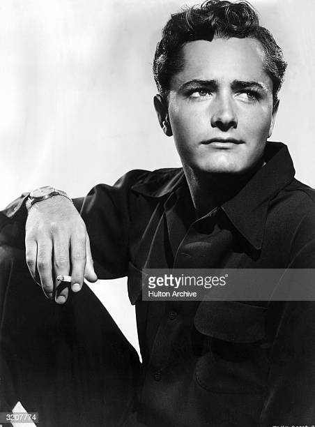 Portrait of American actor John Derek holding a cigarette as he rests his arm on his knee