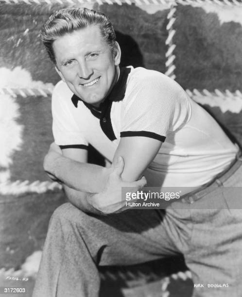 Portrait of American actor Kirk Douglas posing with one leg on a stool and resting his elbow on his knee. Douglas is standing in front of a cow-hide...