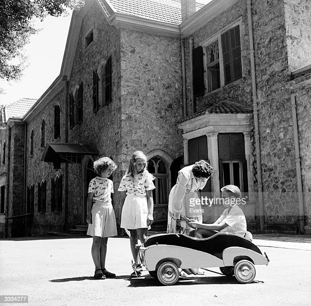 Queen Frederika of Greece with Princess Irene, Princess Sophie and Crown Prince Constantine playing with a toy car in the garden of their summer home...