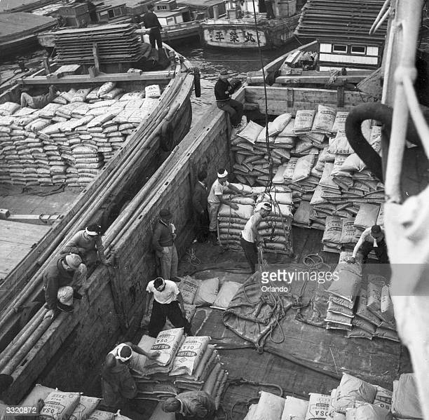 Sacks of sugar being loaded from barges in Tokyo harbour