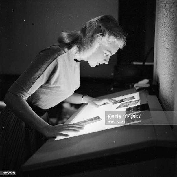Secretary Ginger Stanley checks the negatives of advertising shots in which she is the subject at Silver Springs Florida