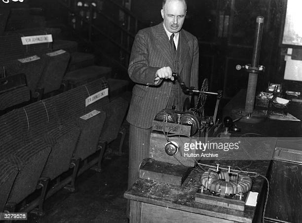 Sir William Lawrence Bragg , director of The Royal Institution, demonstrating electrical effects, by turning a generator handle?.