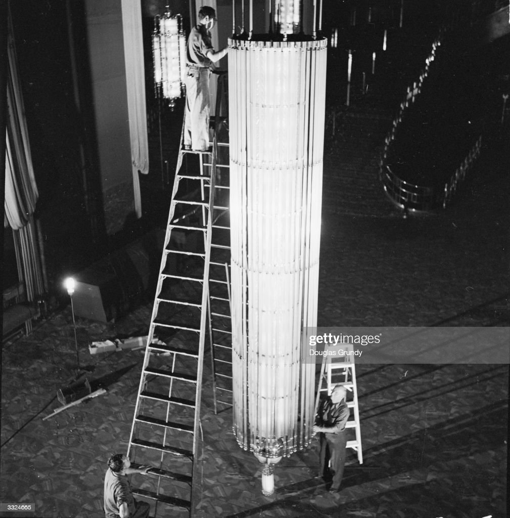 Stage hands erecting the huge Art Deco chandelier which will hang over the grand staircase in the lobby of Radio City Music Hall, New York City.