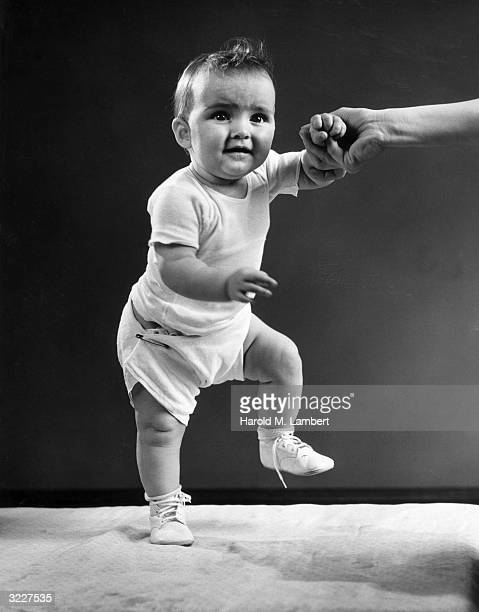 Studio image of a baby standing and raising one foot while holding its mother's hand for help