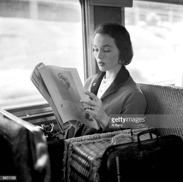 Successful New York fashion model Ginny Cavanaugh reads a magazine whilst commuting to the city