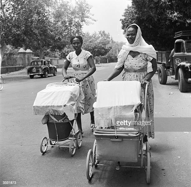 Sudanese women working as nannies for British colonial families push their charges along in prams in a street at Khartoum