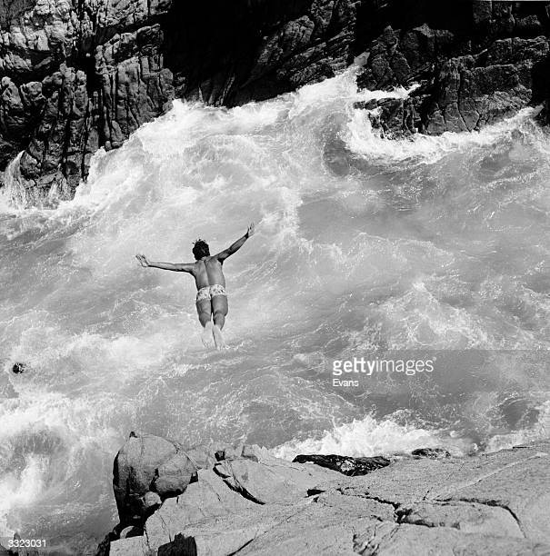 Swimmer diving into rough water lashing against rocky cliffs at Acapulco the Riviera of Mexico