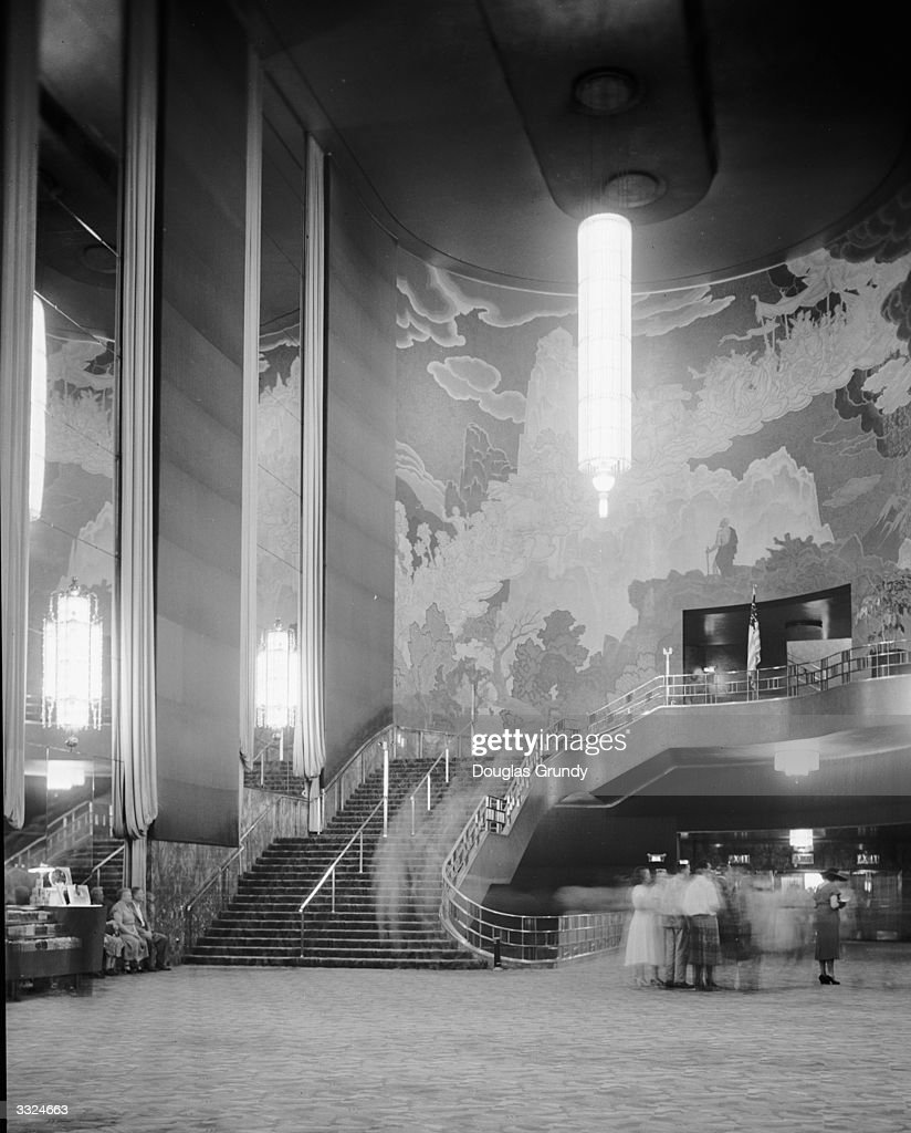 The grand staircase, with a huge vertical Art Deco chandelier and wall mural in the lobby of Radio City Music Hall in New York City.