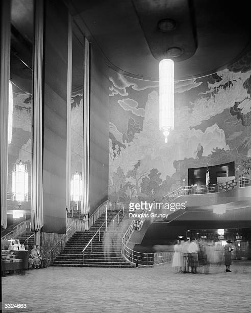 The grand staircase with a huge vertical Art Deco chandelier and wall mural in the lobby of Radio City Music Hall in New York City