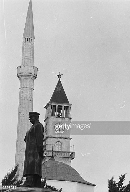 The statue of Joseph Stalin which dominates Skanderbeg Square at Tirana the capital of Albania The minaret of a mosque and the clocktower of a Roman...
