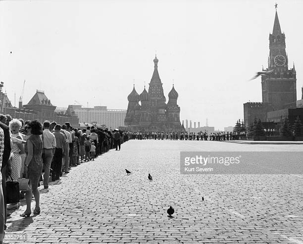 Tourists form a queue in Moscow's Red Square to enter the Mausoleum housing the remains of Vladimir Ilich Lenin In the central background are the...