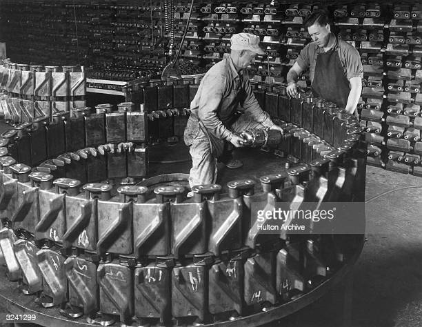 Two American factory workers assemble and install center guides in tank track links for U.S. Army tanks to be used during the Korean War. The links...