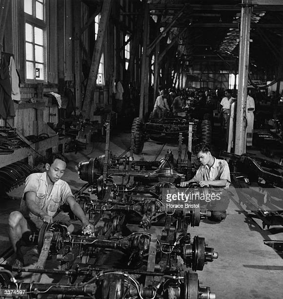 Two factory workers putting the finishing touches to car axles on a production line