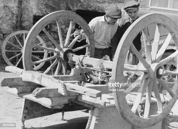 Two men inspect the wellconstructed undercarriage of a small cart which fares better on the mountain roads than most modern vehicles