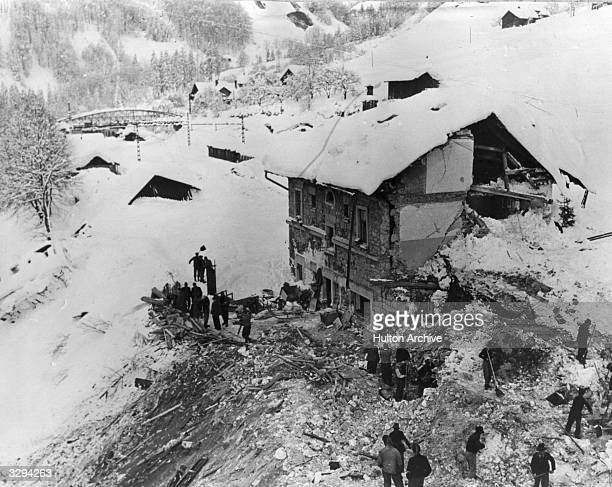 Volunteers dig out an avalanche damaged house in the Vorarlberg Austria
