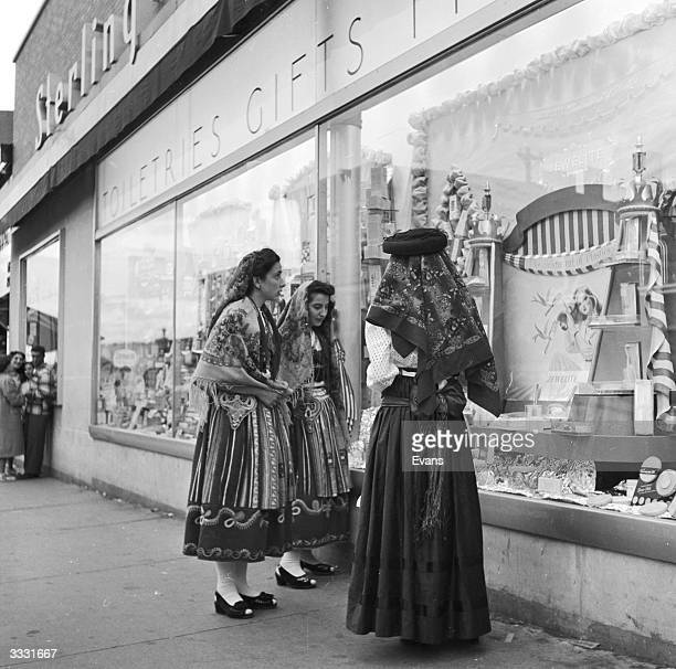 Women of Portuguese descent window shopping in the fishing town of Gloucester, Massachusetts.