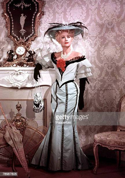 Circa 1950s A portrait of an elegant woman standing within a posh house whilst leaning on a mantlepiece she is wearing a light blue dress which has...