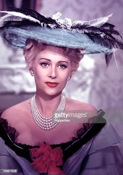 Circa 1950s A portrait of an elegant woman wearing a light blue dress which has black seems and a wide brimmed feathered hat She also has a necklace...