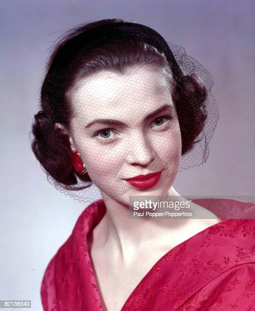 Circa 1950s A Portrait Of Dark Haired Girl Wearing A Fasionable Red Vnecked Evening Dress And