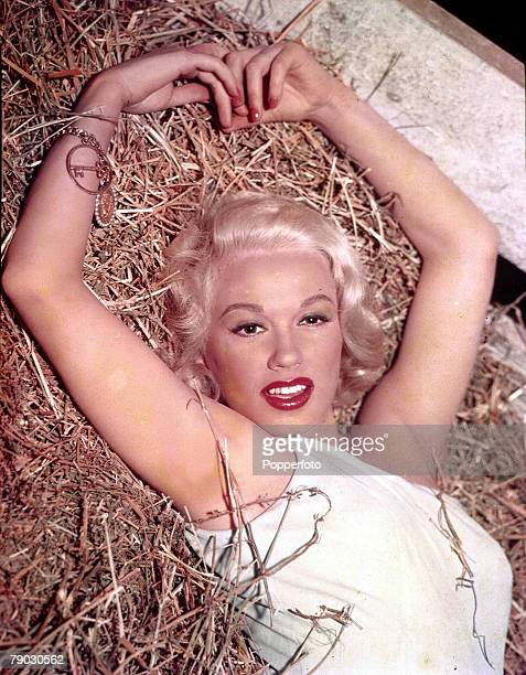 Circa 1950's, American actress Mamie Van Doren lying seductively in the hay